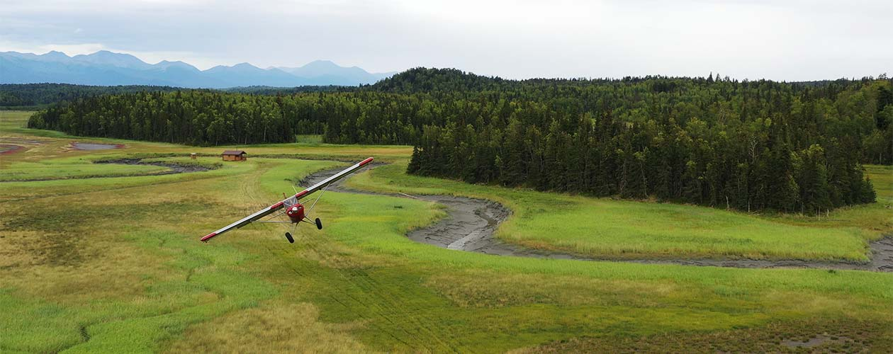 Tailwheel aircraft departing from grass airstrip